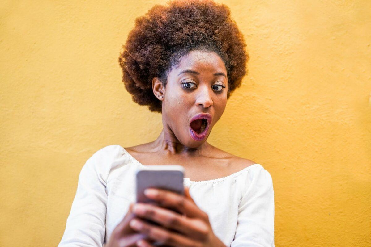 Frau guckt geschockt auf ihr Handy.