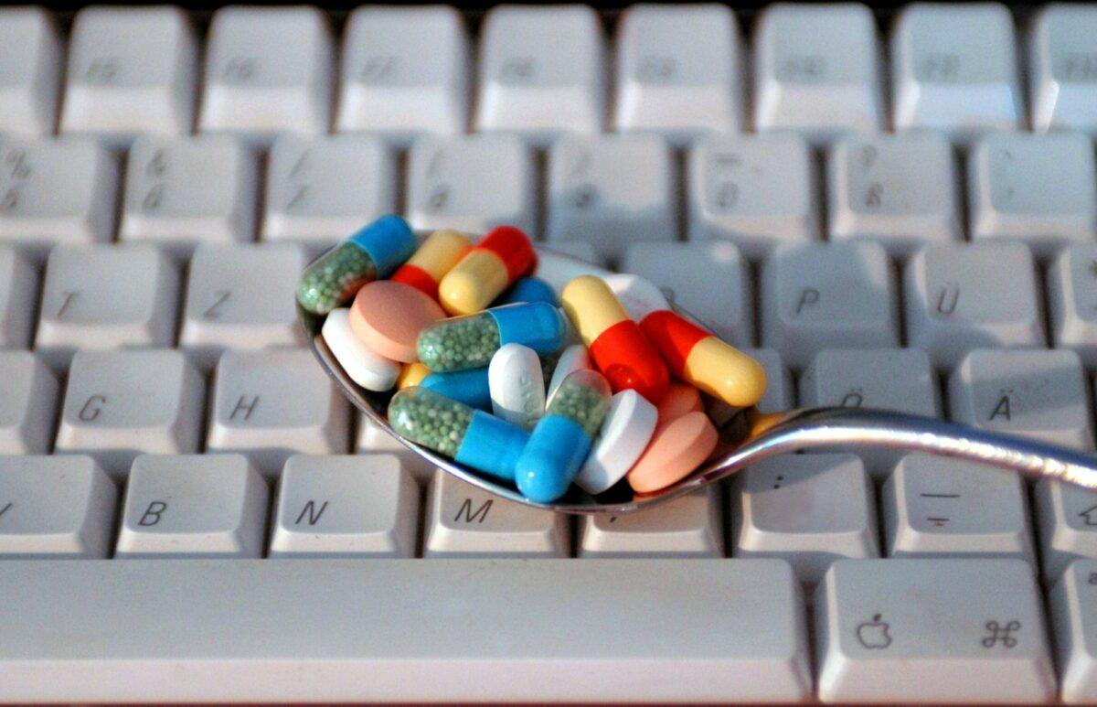 Löffel mit Pillen auf einer Tastatur