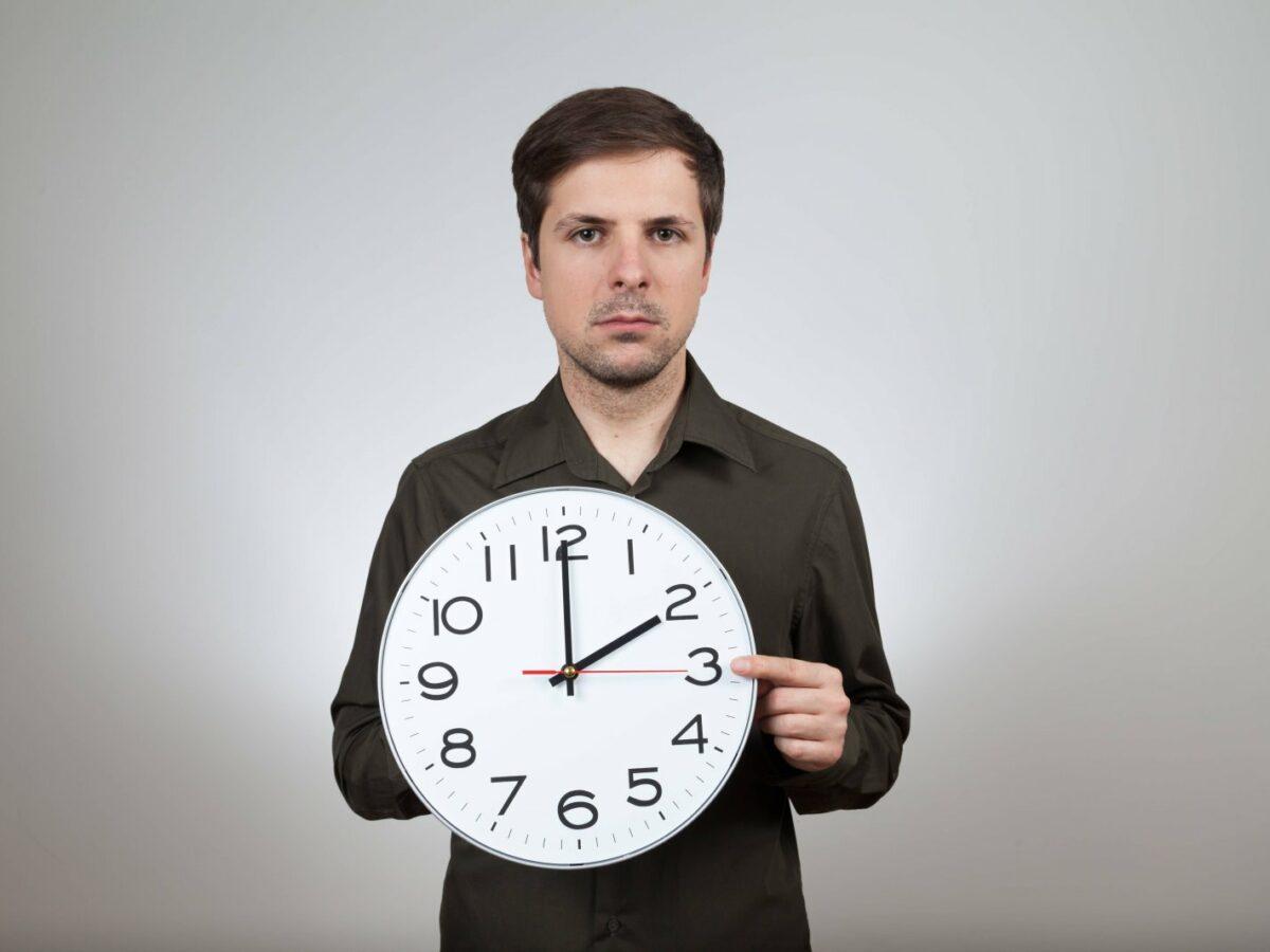 Mann dreht am Zeiger einer Uhr.