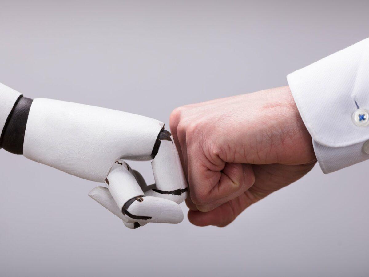 Roboterhand und Menschenhand geben sich eine Faust.