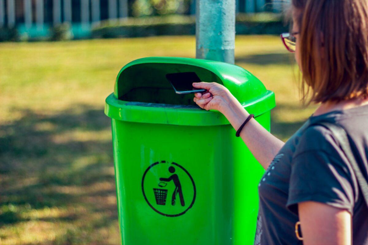 Frau wirft ein Handy in eine Recycling-Tonne.