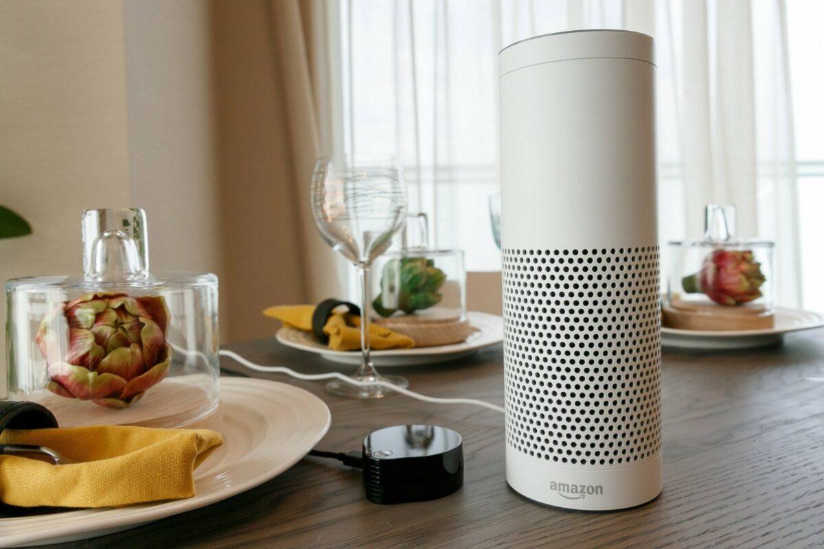 Amazon Echo-Lautsprecher steht auf einem Tisch mit Gläsern und Deko