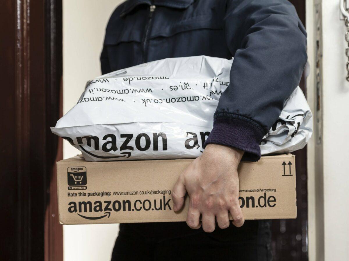 Amazon-Lieferbote hält zwei Pakete im Arm
