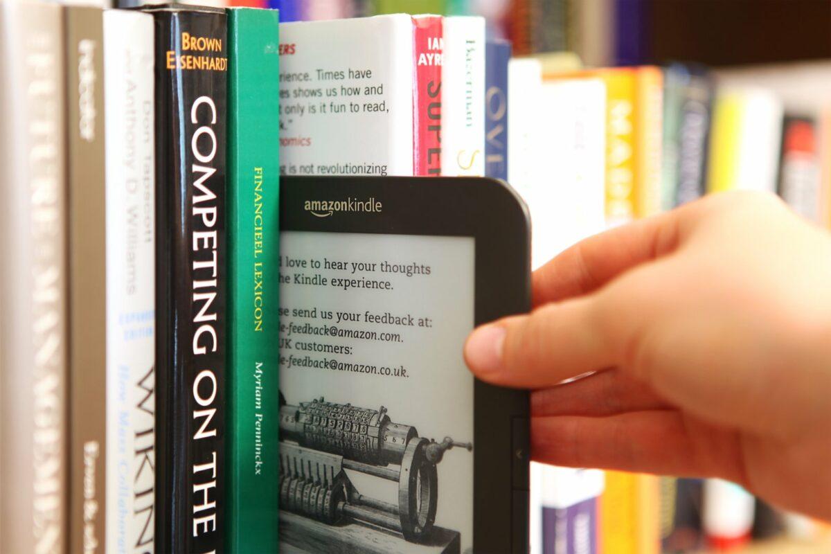 eBook-Reader Kindle von Amazon wird aus Bücherregal gezogen