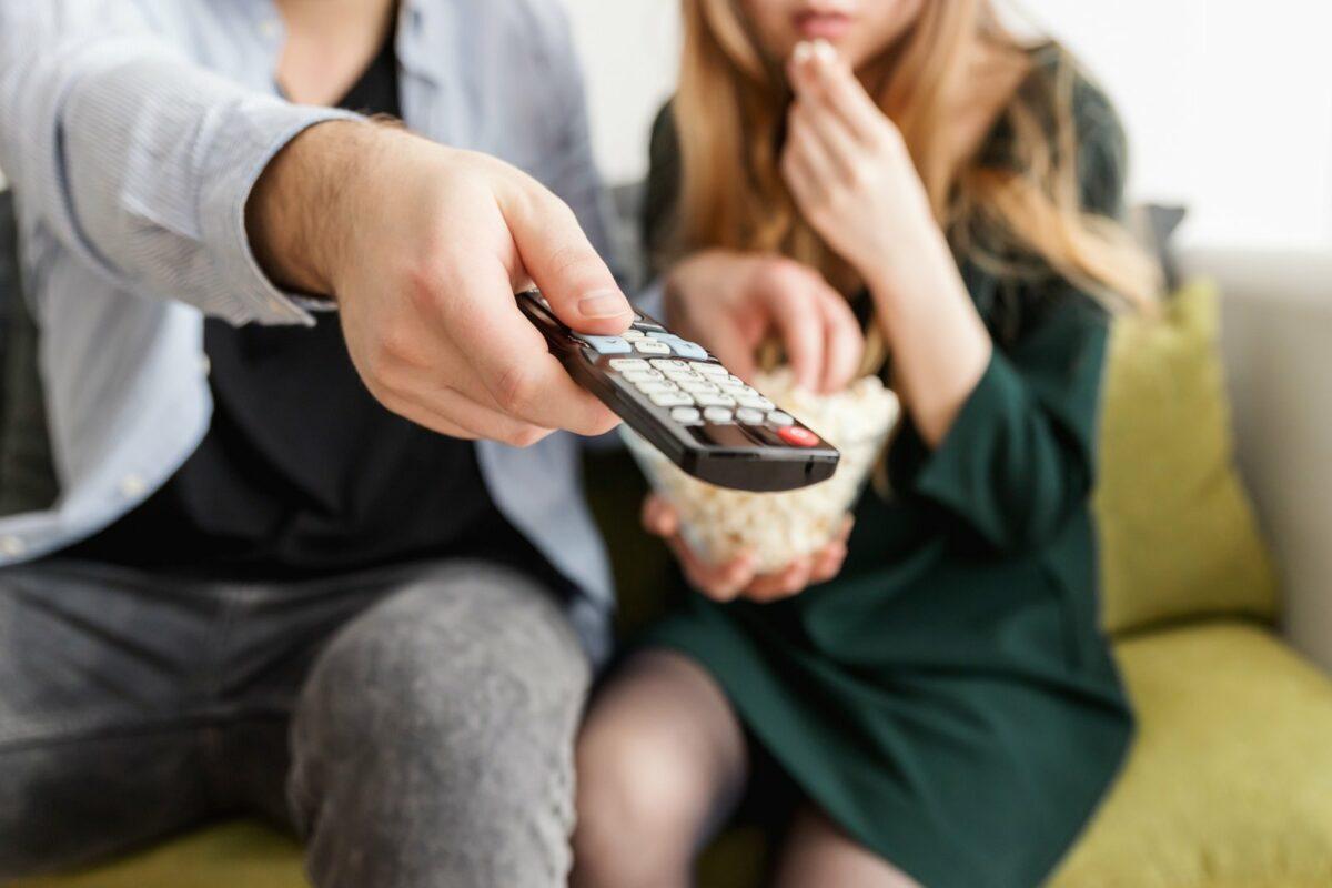 Ein Paar schaut TV und isst Popcorn.