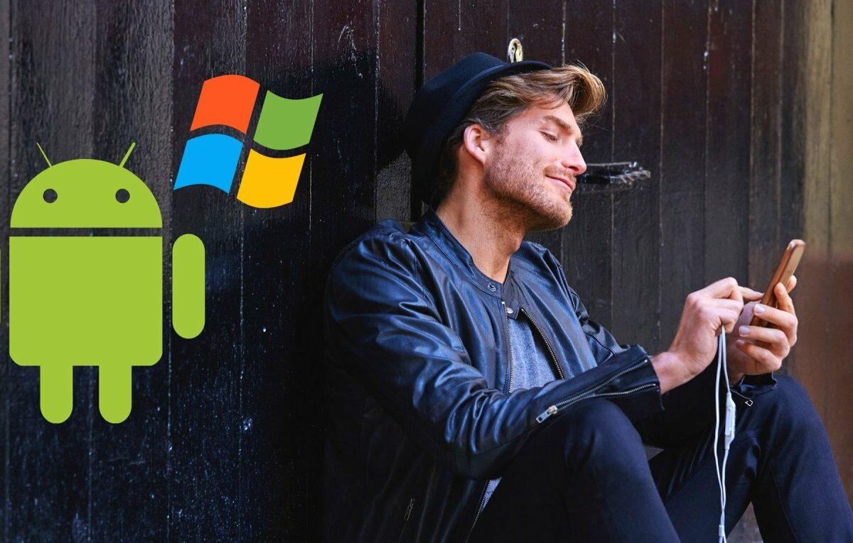 Mann mit Smartphone und die Logos von Android und Windows