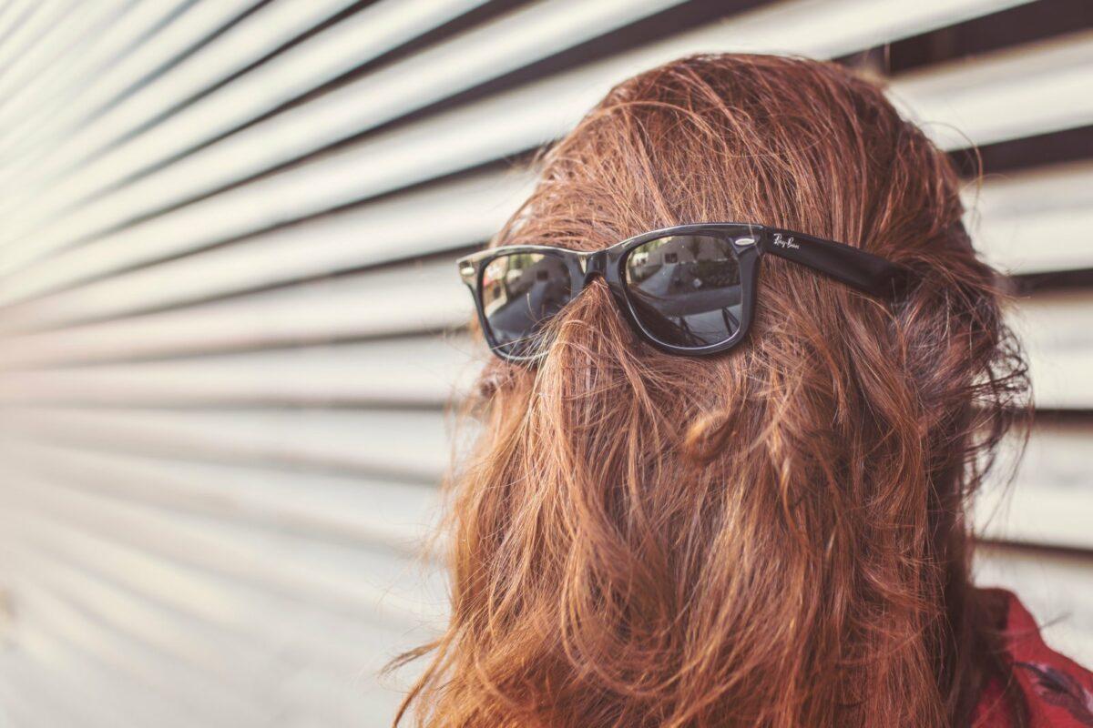 Frau mit Haaren im Gesicht und Sonnenbrille