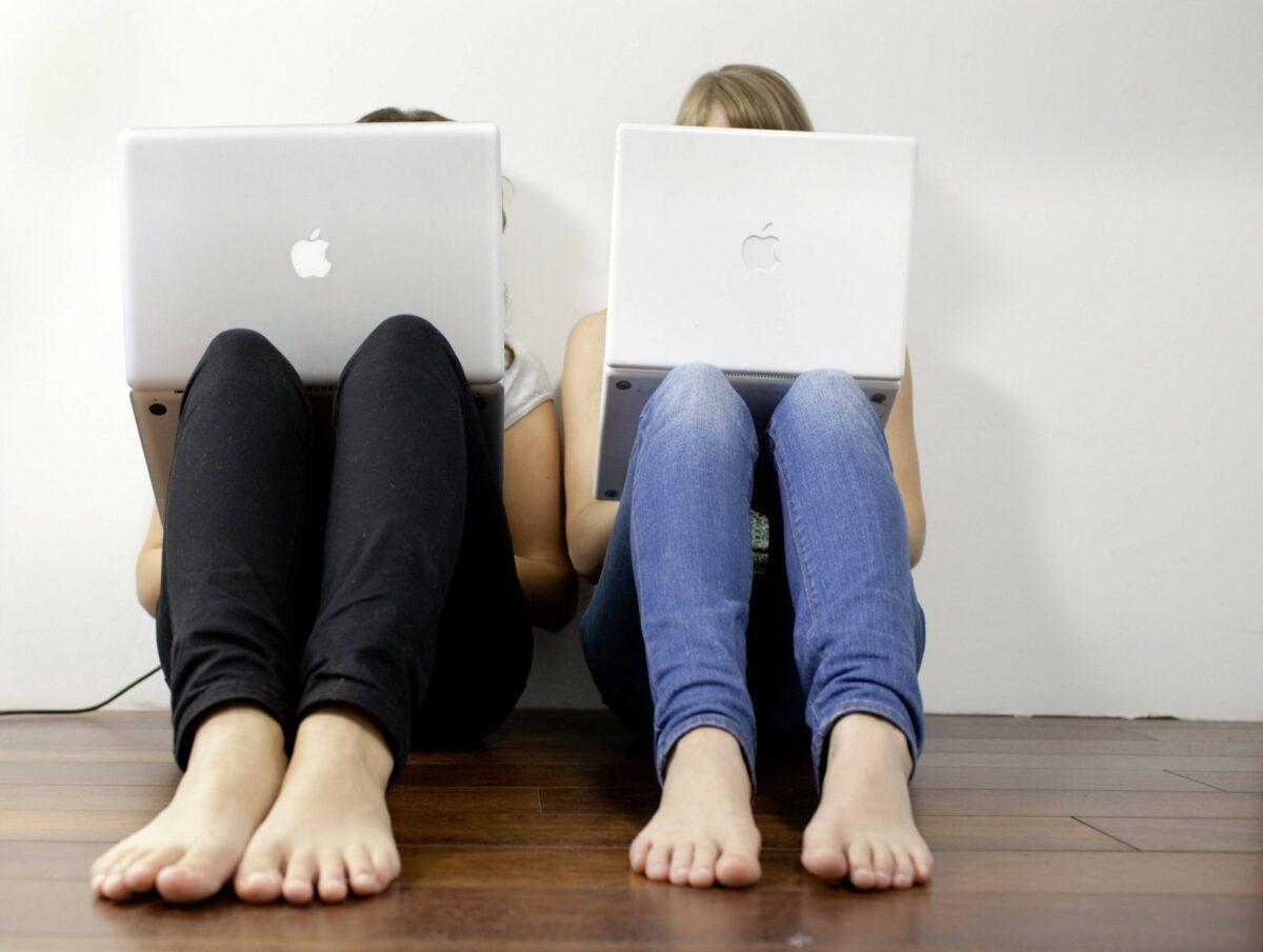 Zwei Frauen sitzen versteckt hinter ihrem Laptop