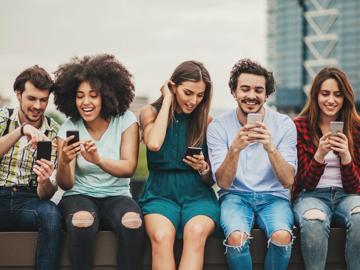 Fünf Freunde sitzen nebeneinander und blicken auf ihr Handy.