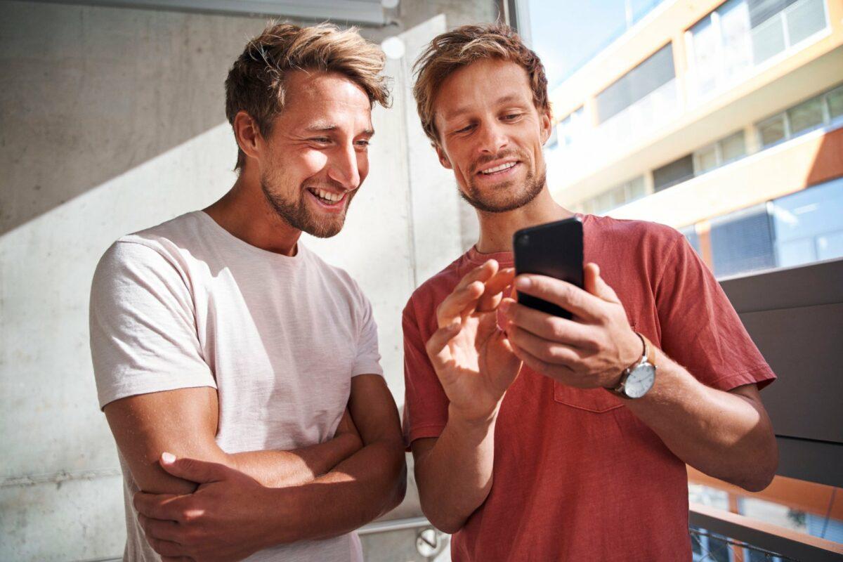 Ein Mann zeigt einem anderem Mann etwas auf seinem Handy.