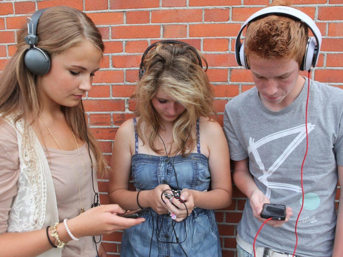 drei jugendliche hören spotify auf dem handy