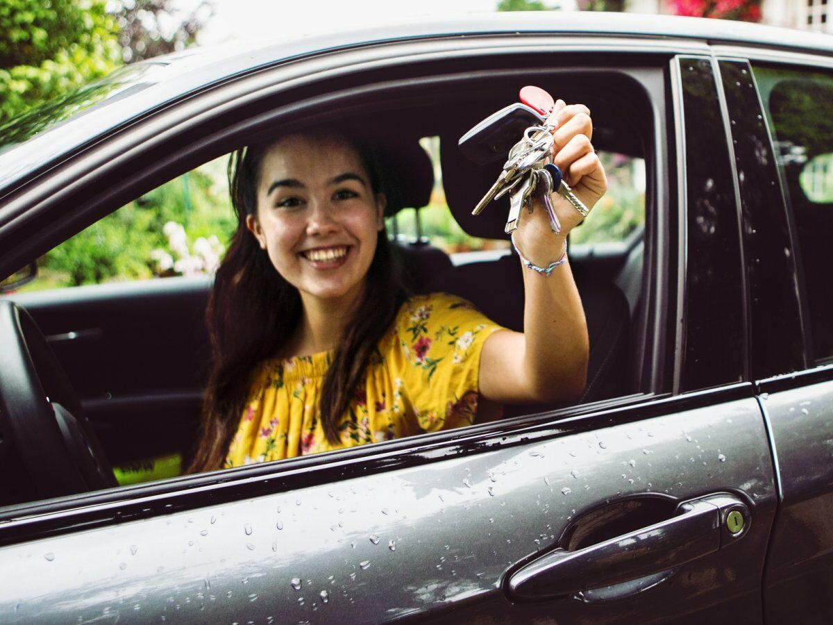 Frau freut sich über ein neues Auto