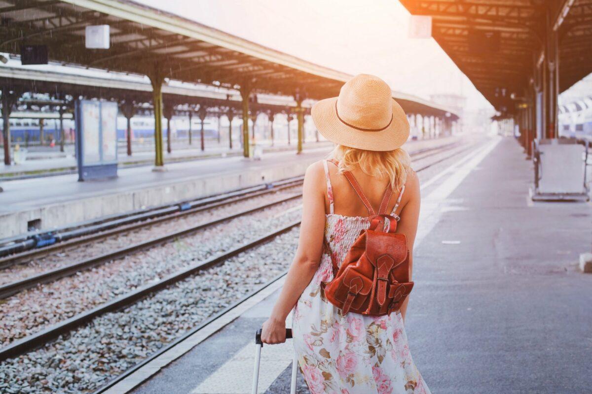 Frau am Bahnhof mit Koffer
