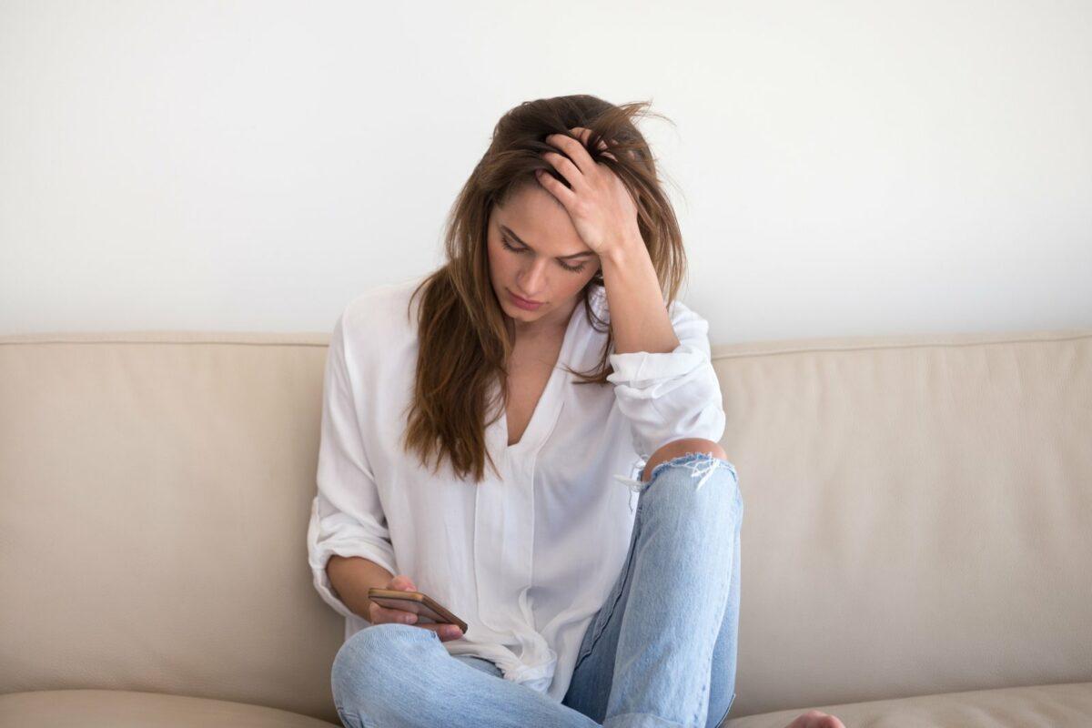 Frau mit Handy besorgt auf dem Sofa