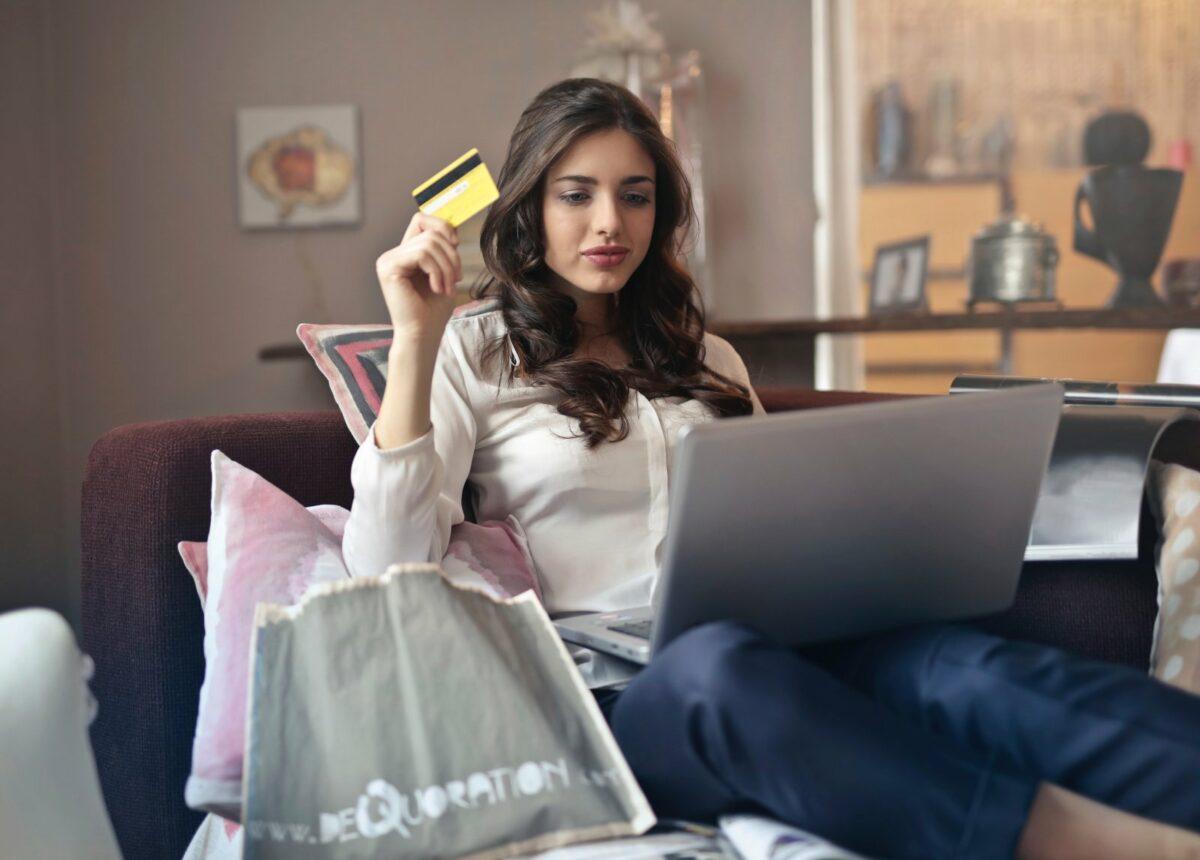 Frau sitzt mit ihrem Laptop auf dem Sofa