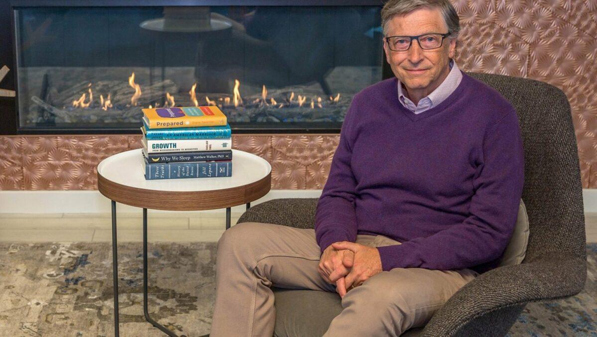 Bill Gates mit Büchern vorm Kamin.