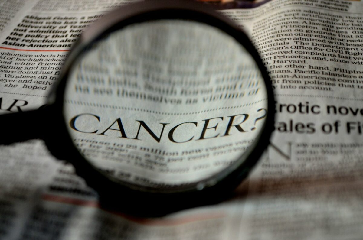 Ein Zeitungartikel über Krebs wird durch eine Lupe lesbar