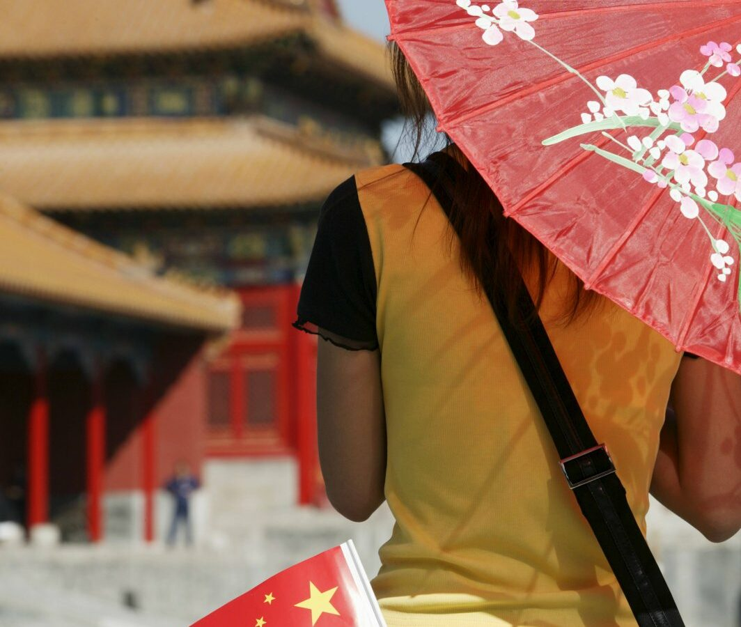 Frau mit chinesischem Schirm vor einer chinesischen Pagode.