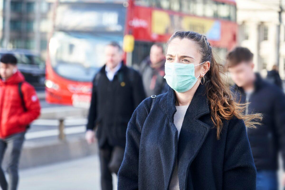 Frau mit Schutzmaske in der Stadt.
