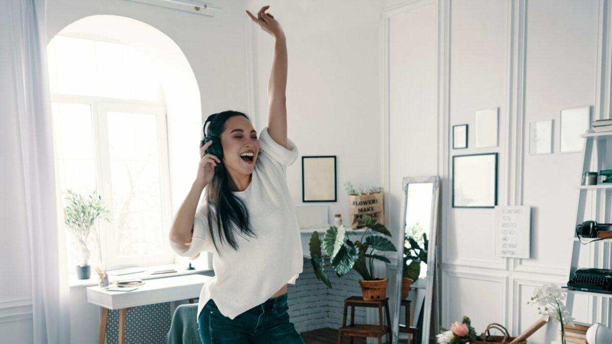 Frau hört Musik mit Kopfhörern und tanzt.