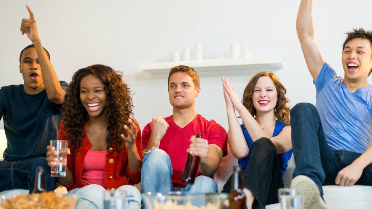 Fünf Freunde sitzen auf dem Sofa und freuen sich über etwas
