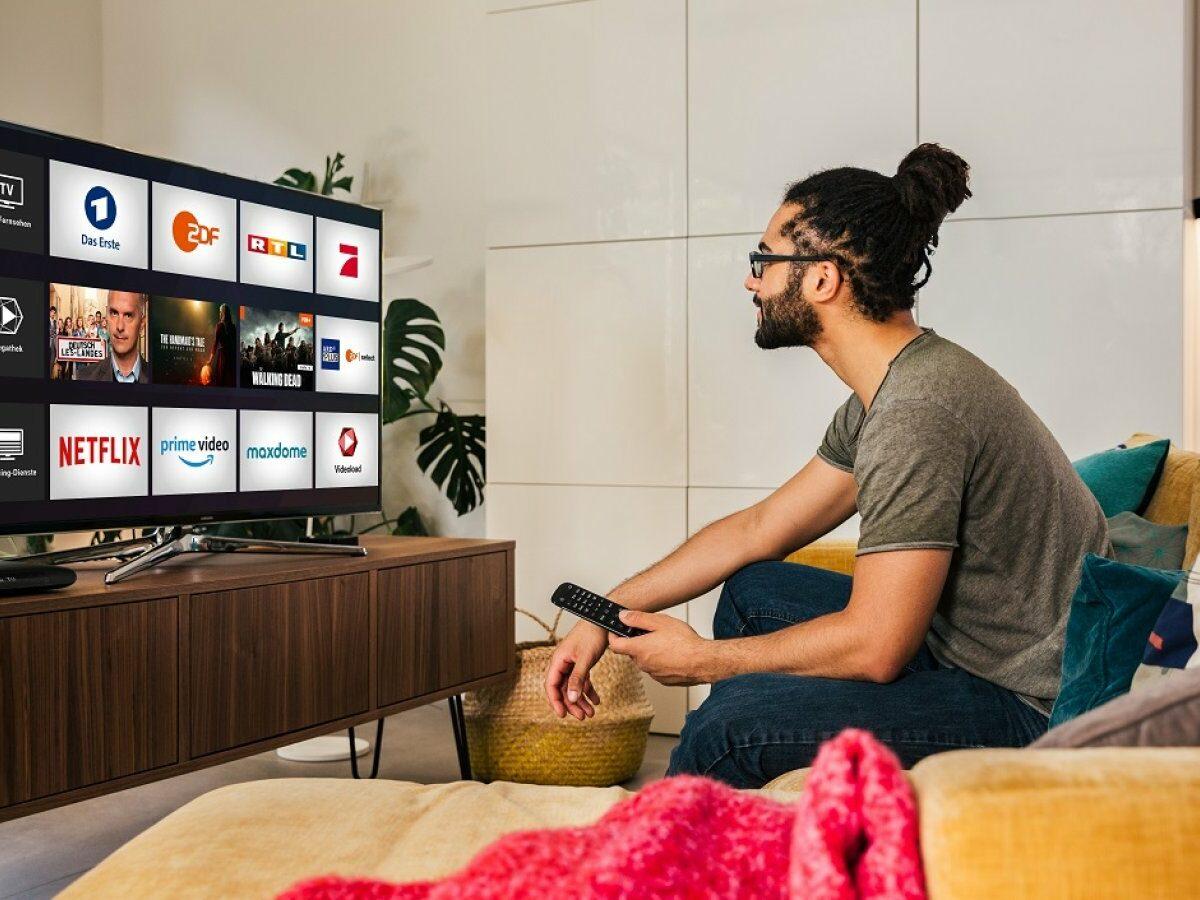 Mann vor Fernseher mit MagentaTV-Oberfläche.
