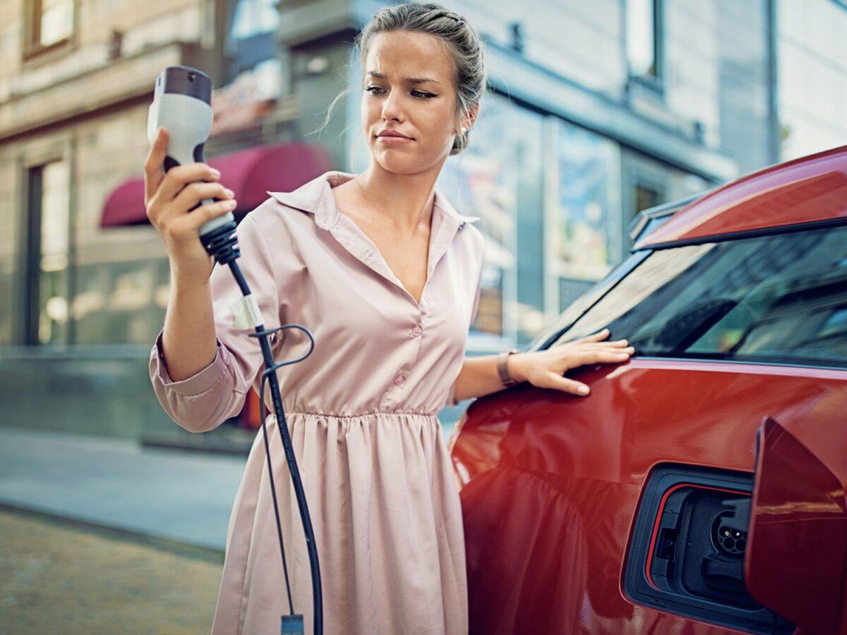 Frau beim Aufladen eines Elektroautos