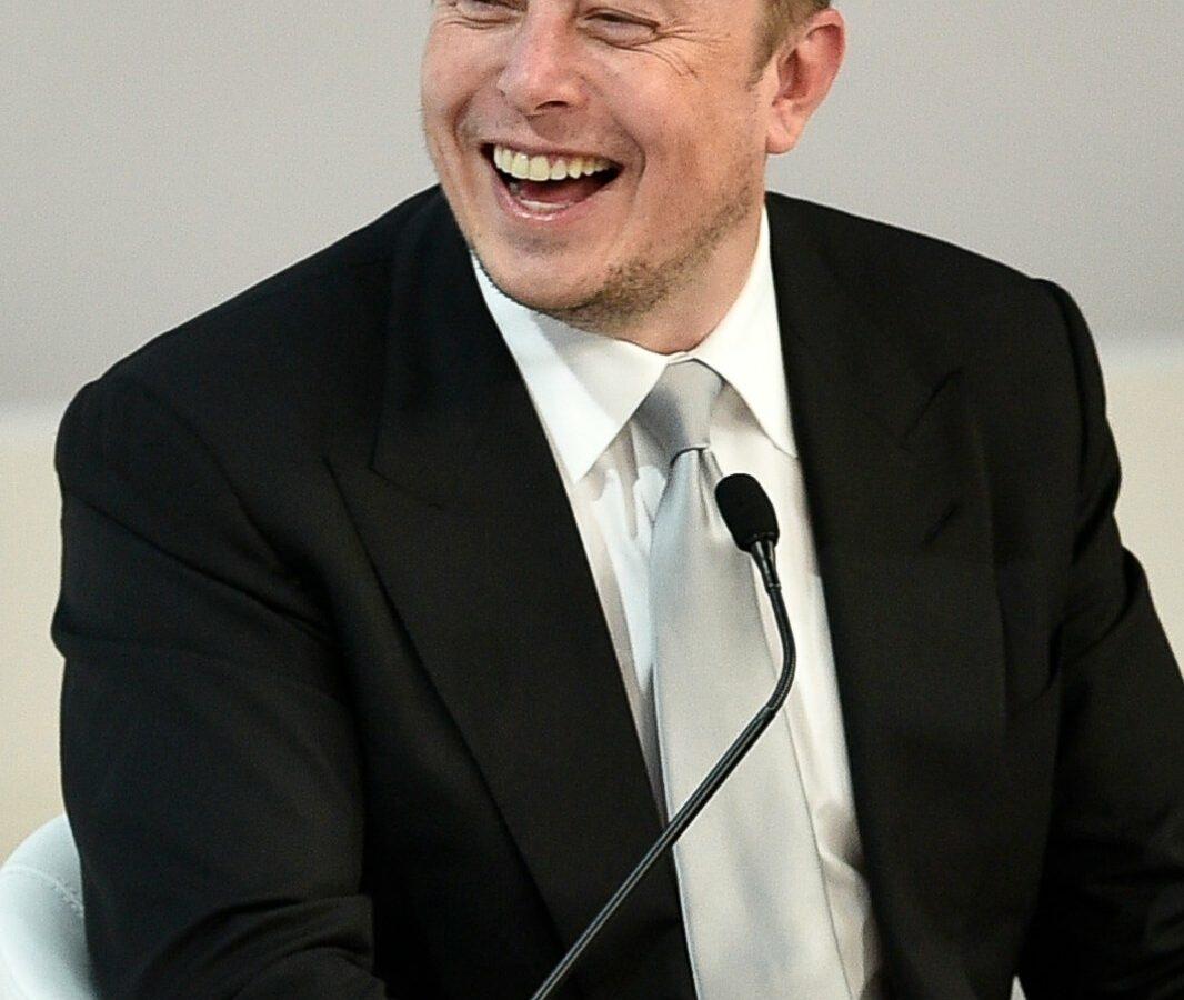 Elon Musk sitzt lachend vor einem Mikrofon