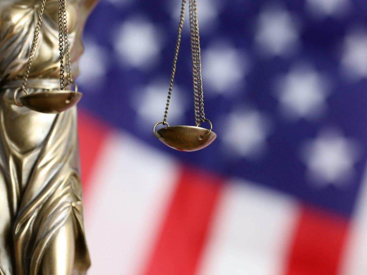 Justitia vor einer US-Flagge