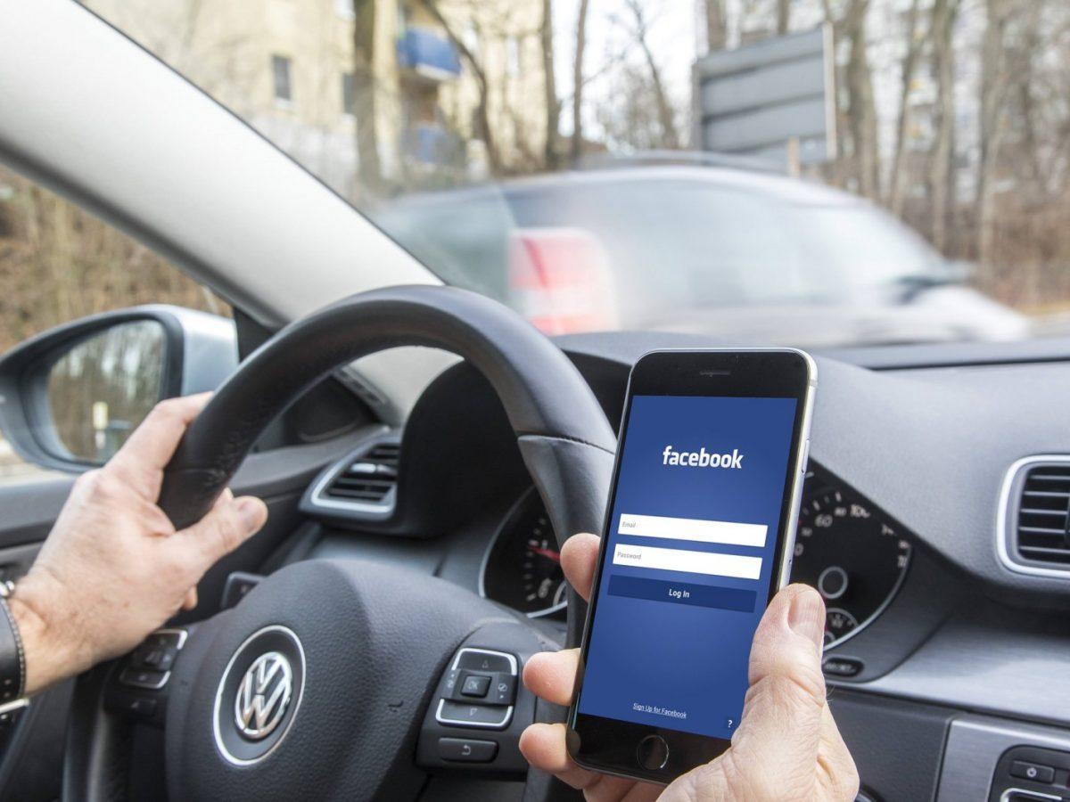 Mann im Auto mit Facebook auf dem handy