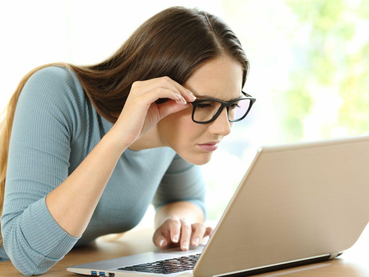 Frau schaut skeptisch auf ihren Laptop