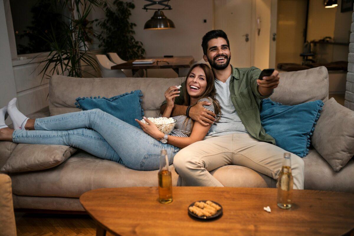 Paar guckt fernsehen auf dem Sofa