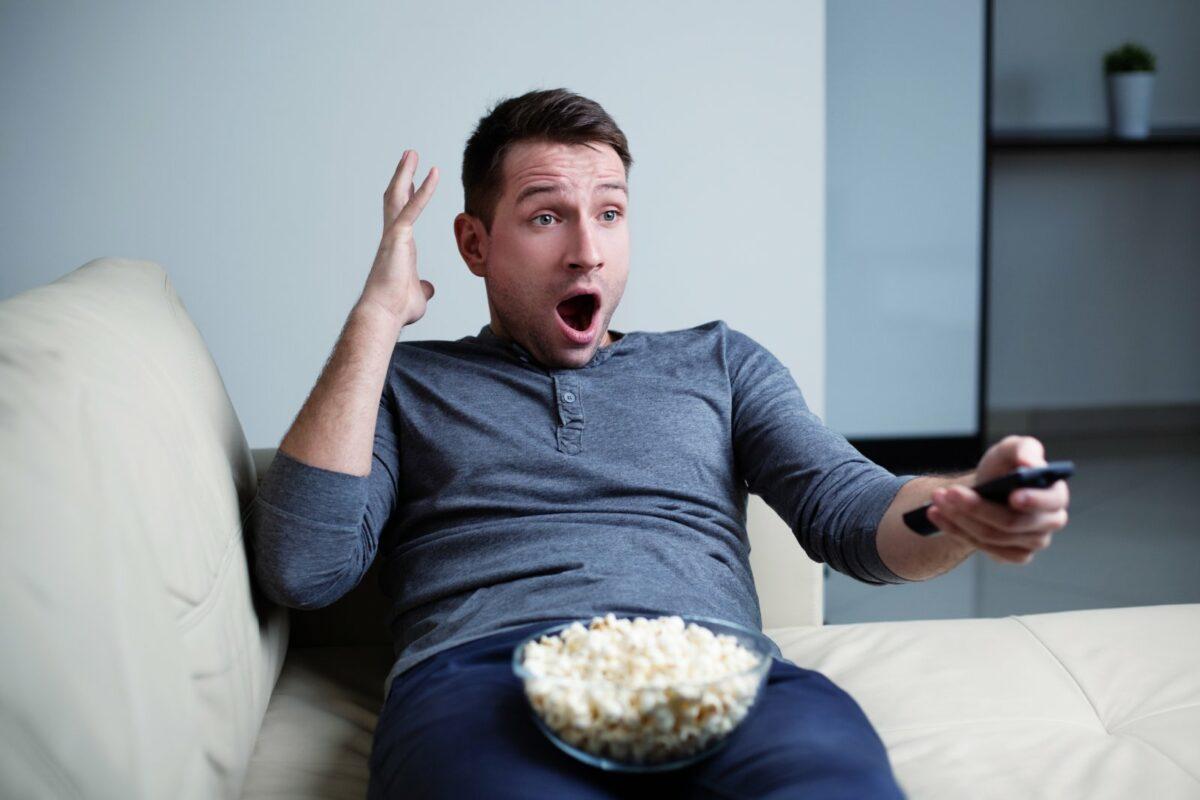 Ein Mann sitzt mit Popcorn erschrocken vor dem Fernseher.