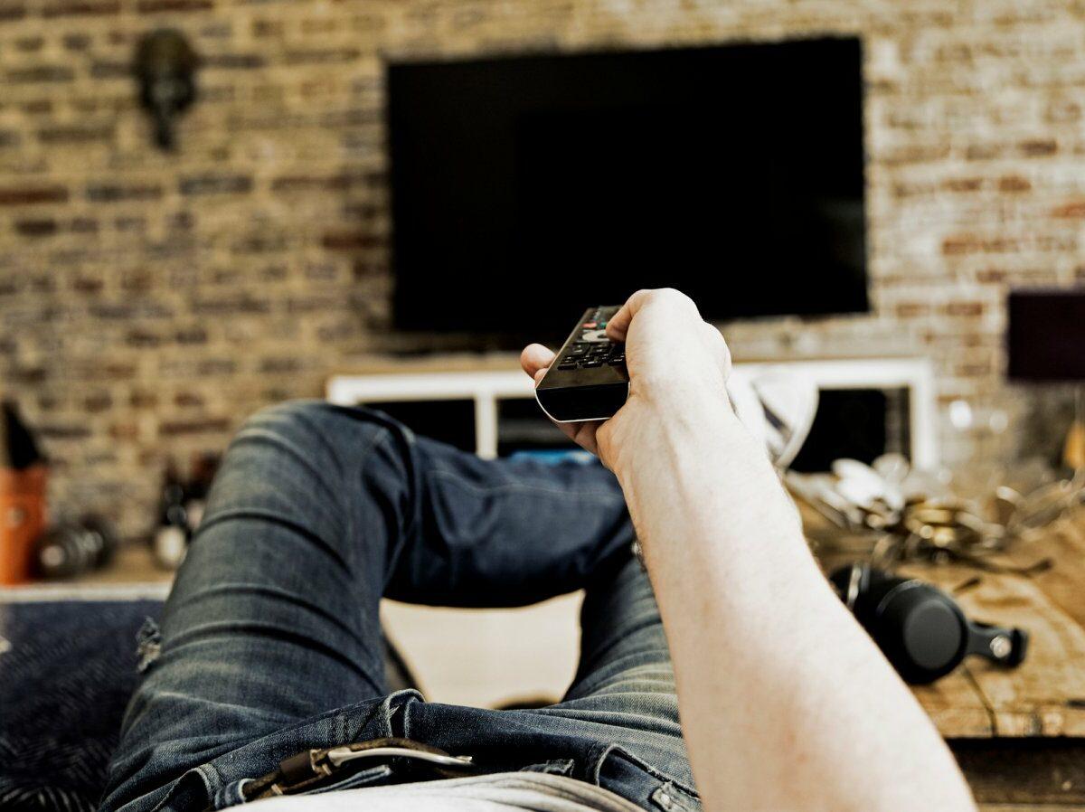 Jemand hat Fernbedienung in der Hand und schau TV.