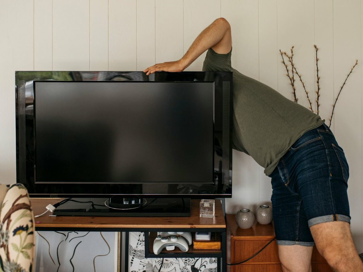 Mann versucht Fernseher zu reparieren.