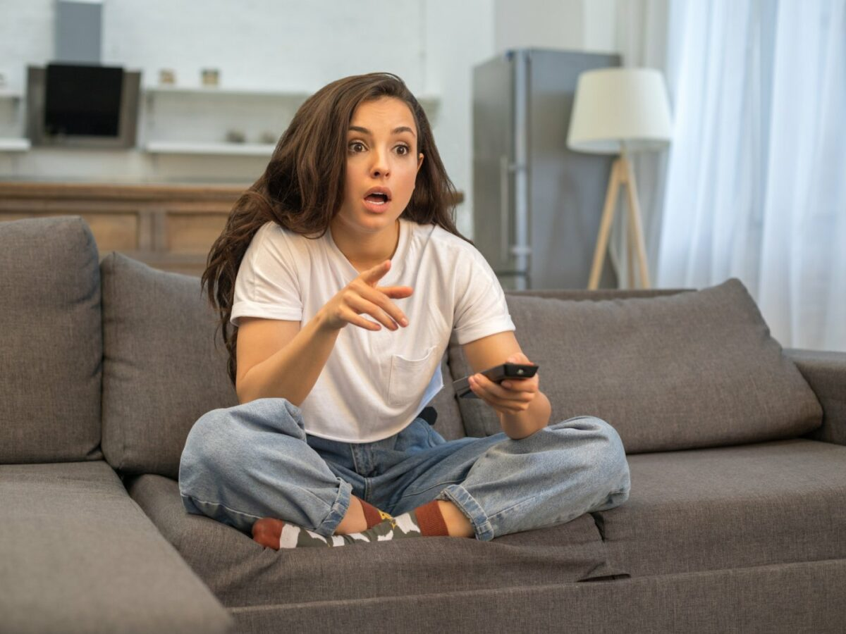 Frau erschrocken vorm Fernseher.