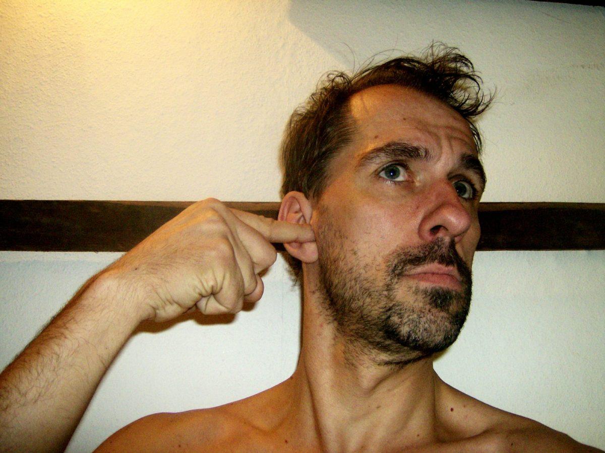 Mann steckt Finger ins Ohr