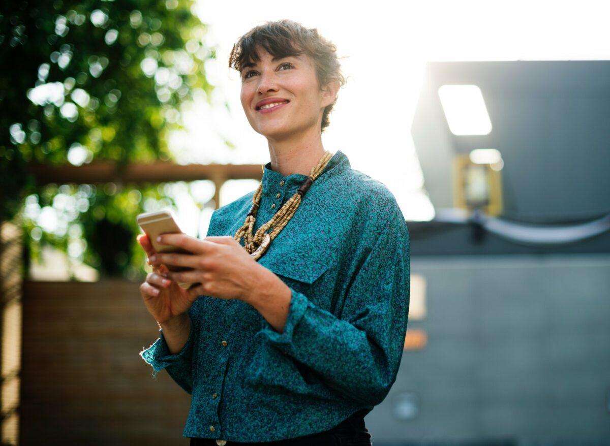 Glückliche Frau mit Handy in der Hand