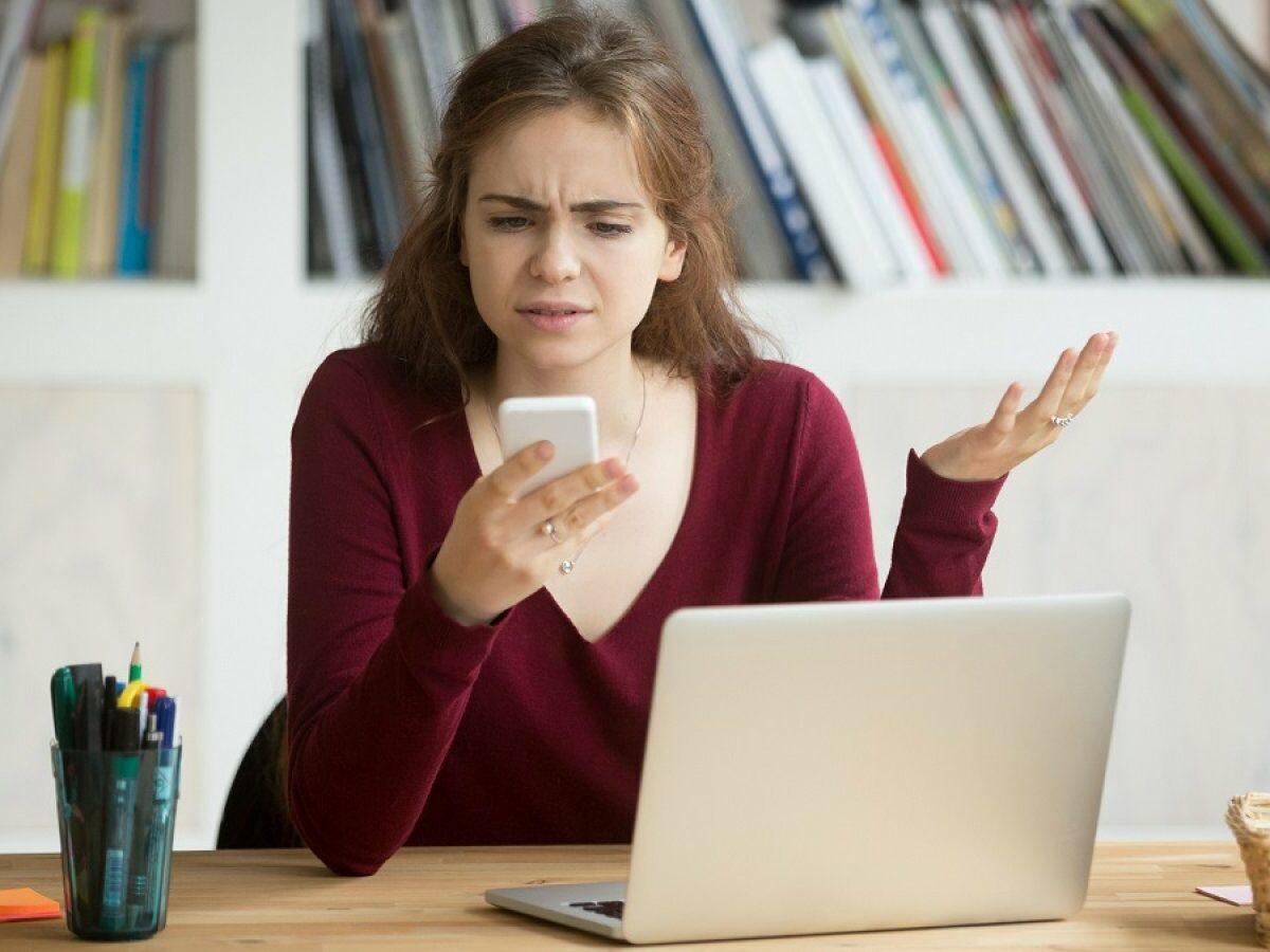 Frau mit Handy in der Hand ist sauer.