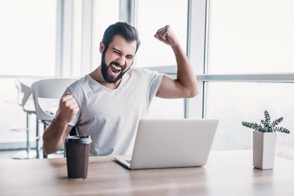 Mann freut sich vor PC