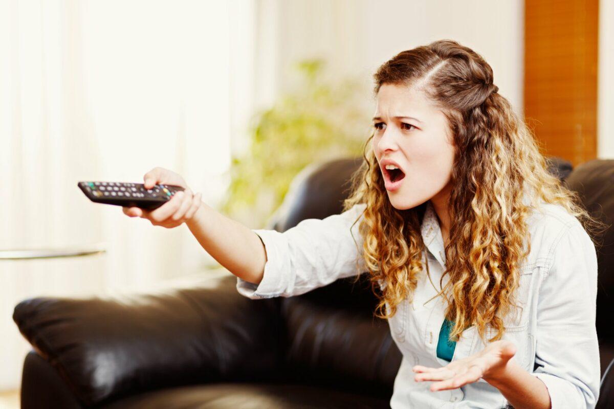 Frau zielt mit einer Fernbedienung ärgerlich auf einen Fernseher.
