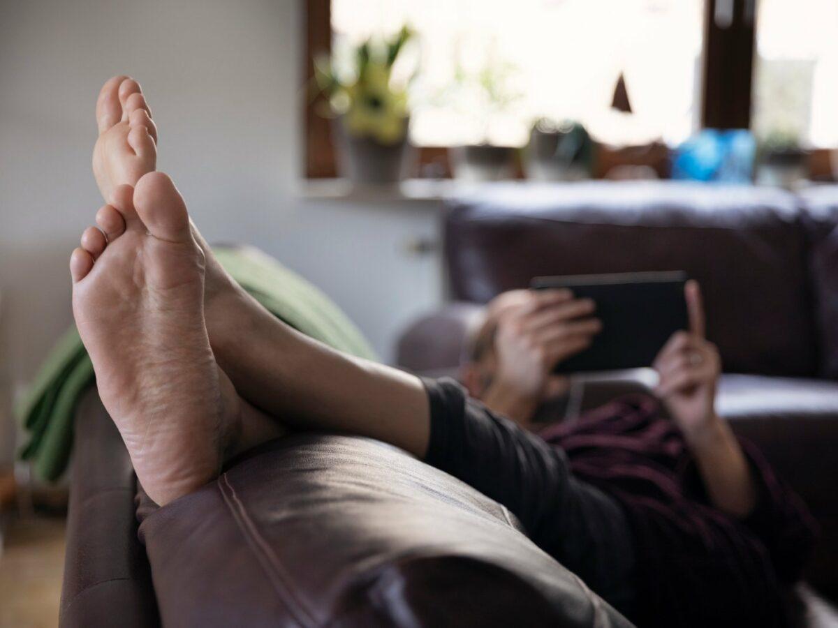 Person legt auf der Couch die Füsse hoch