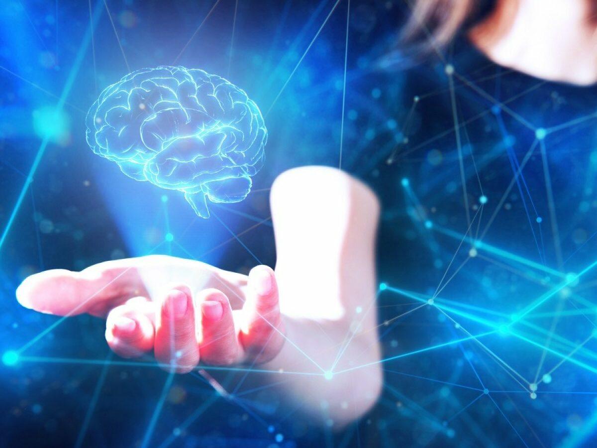 Gehirn-Hologram schwebt über der Hand einer Frau.