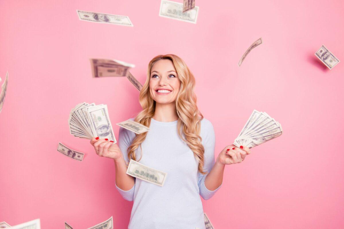 Frau wirft mit Geldscheinen um sich.