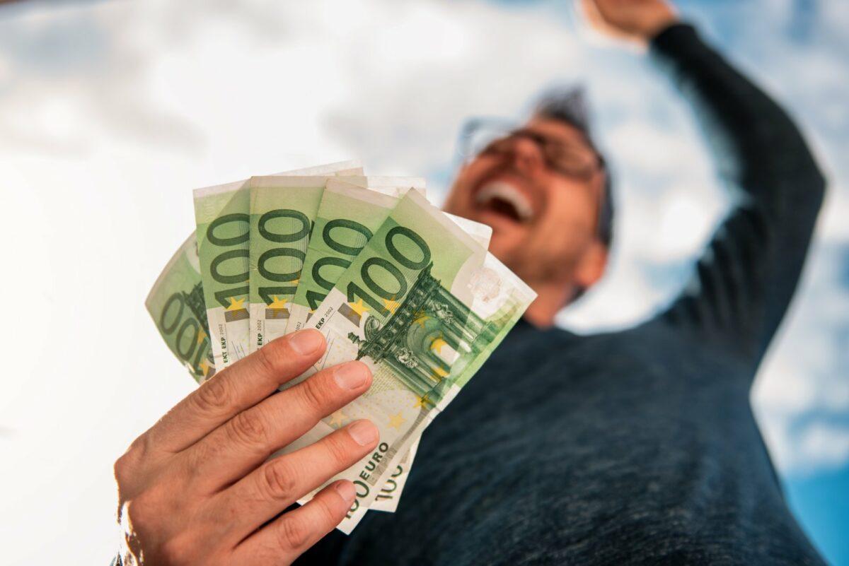 Mann freut sich über viele 100-Euro-Scheine.