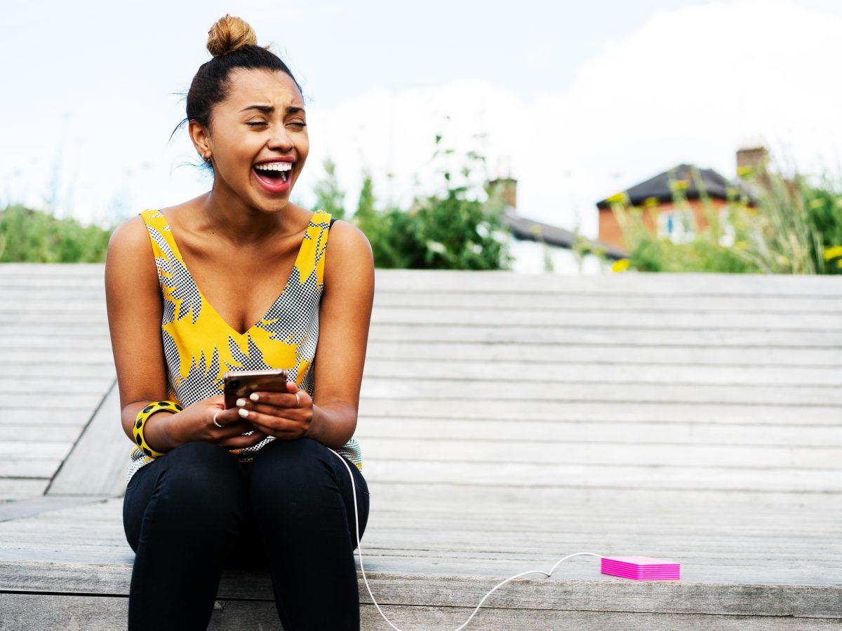 Frau lacht mit Handy in der Hand