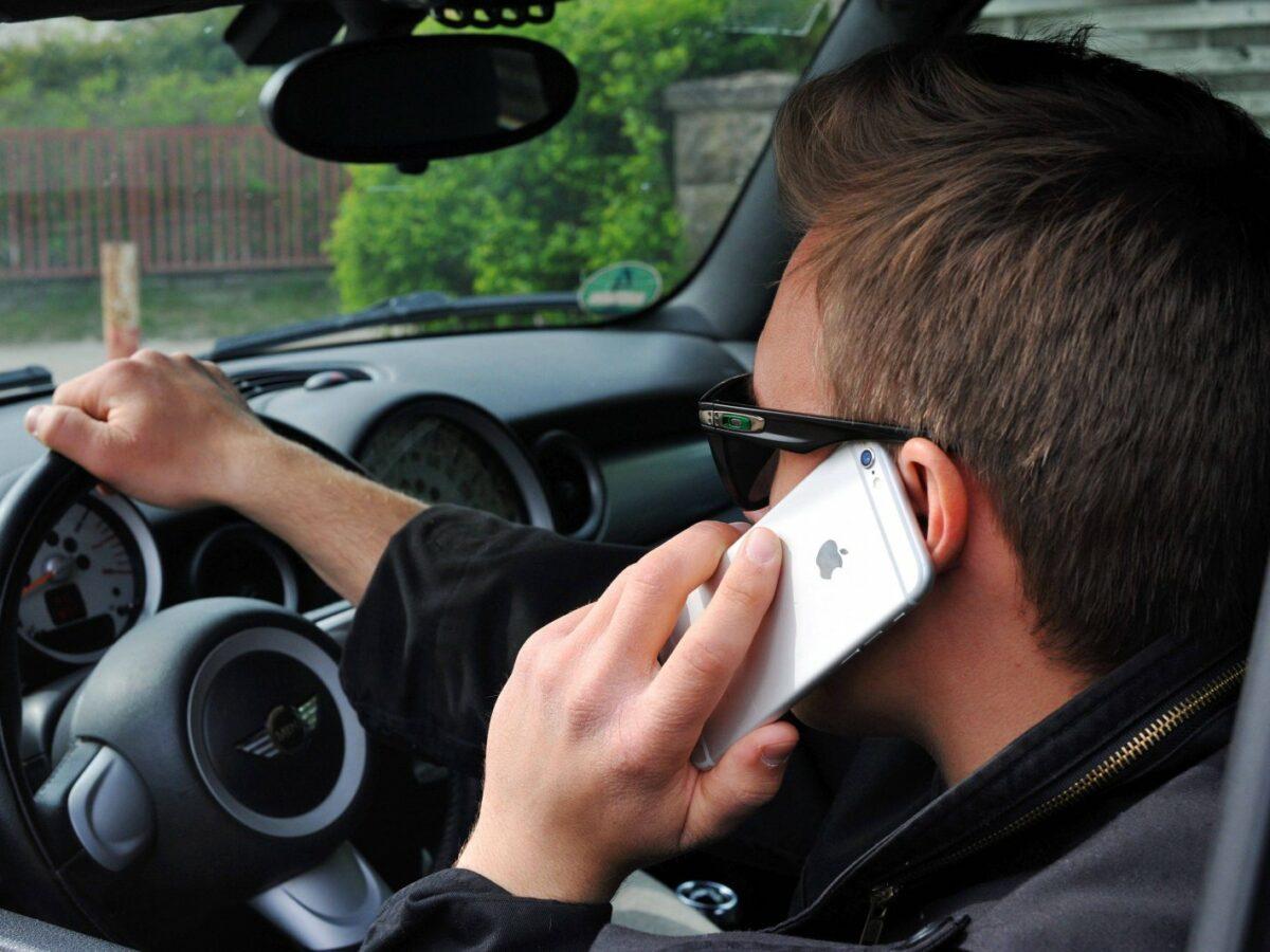 Mann mit Sonnenbrille telefoniert beim Autofahren mit seinem Handy.