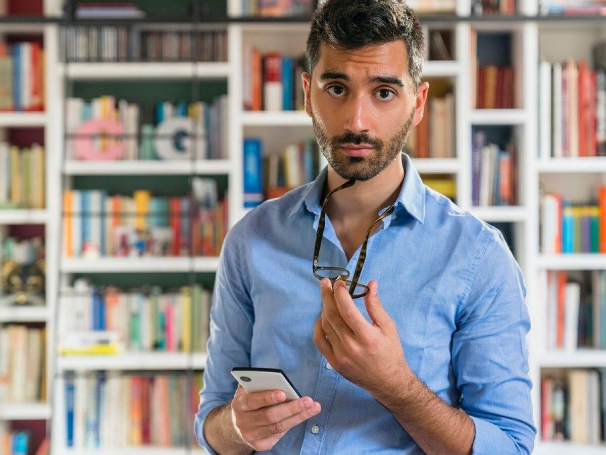 Mann mit Handy schaut misstrauisch.