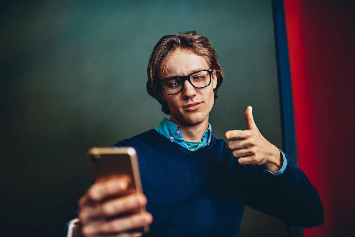 Mann mit gerecktem Daumen schaut überlegen in sein Handy.