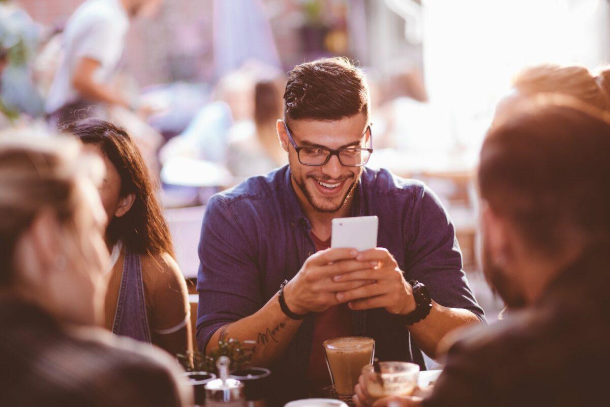 Mann sitzt im Café und schaut lachend auf sein Handy.